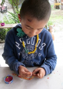 One of the littlest ninos stringing pasta beads